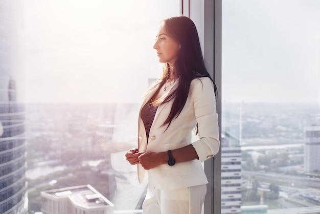Portrait d'une jeune femme pensive et réussie, debout près de la fenêtre au bureau.