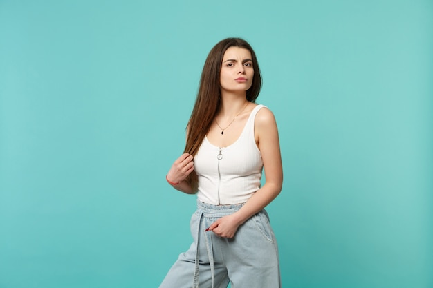 Portrait d'une jeune femme perplexe dans des vêtements légers et décontractés, debout, regardant la caméra isolée sur fond de mur bleu turquoise. les gens émotions sincères, concept de style de vie. maquette de l'espace de copie.
