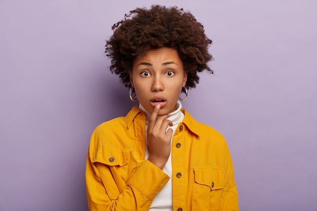 Portrait de jeune femme perplexe nerveuse touche la lèvre inférieure, a une coiffure afro bouclée, une expression anxieuse, porte une veste jaune à la mode et des boucles d'oreilles, des modèles intérieurs sur fond violet