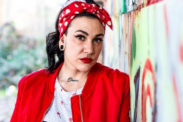 Portrait de jeune femme avec piercings, dilatations et tatouages vêtue d'une veste rouge et d'un arc rouge dans ses cheveux. appuyé contre un mur de graffitis.