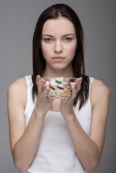 Portrait d'une jeune femme avec des pilules dans une fiole de verre.