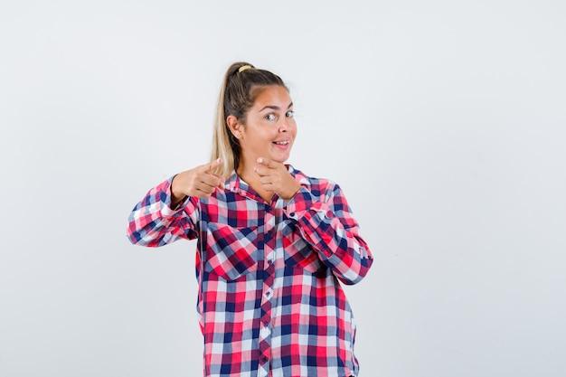 Portrait de jeune femme pointant la caméra en chemise à carreaux et à la vue de face heureux