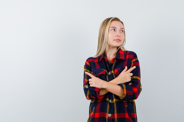 Portrait de jeune femme pointant des deux côtés en chemise à carreaux et à la vue de face hésitante