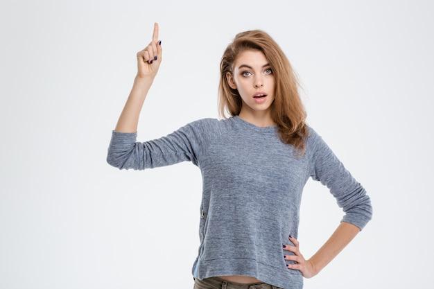 Portrait d'une jeune femme pointant le doigt vers le haut isolé sur fond blanc