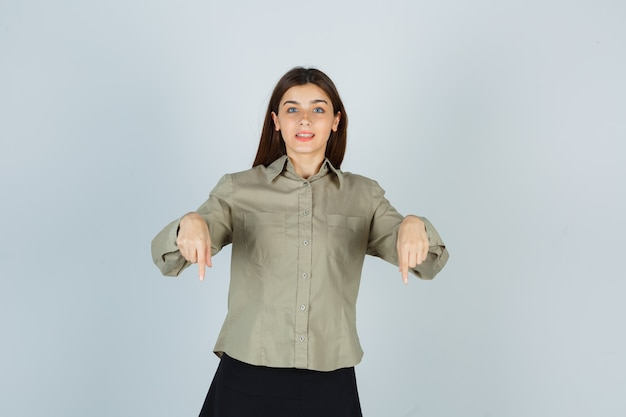 Portrait de jeune femme pointant vers le bas en chemise, jupe et à la joyeuse vue de face