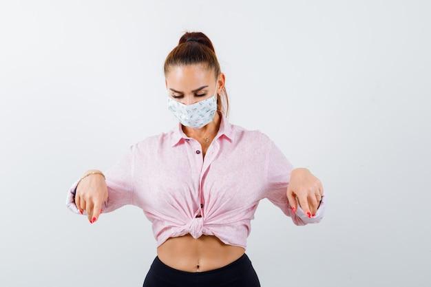 Portrait de jeune femme pointant vers le bas en chemise, masque et à la vue de face ciblée