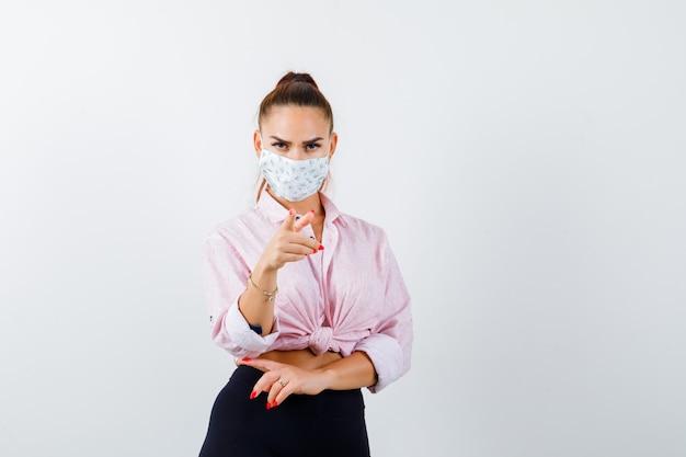 Portrait de jeune femme pointant vers la caméra en chemise, pantalon, masque et à la vue de face nerveuse