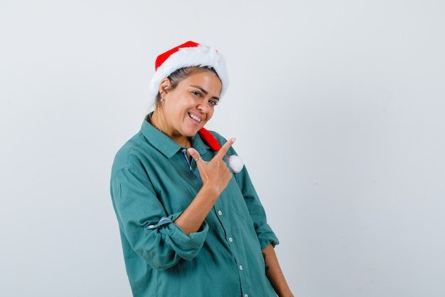 Portrait de jeune femme pointant vers le coin supérieur droit en chemise, bonnet de noel et à la vue de face joyeuse
