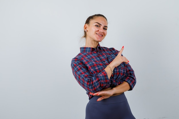 Portrait de jeune femme pointant vers le coin supérieur droit en chemise à carreaux, pantalon et à la vue de face heureuse