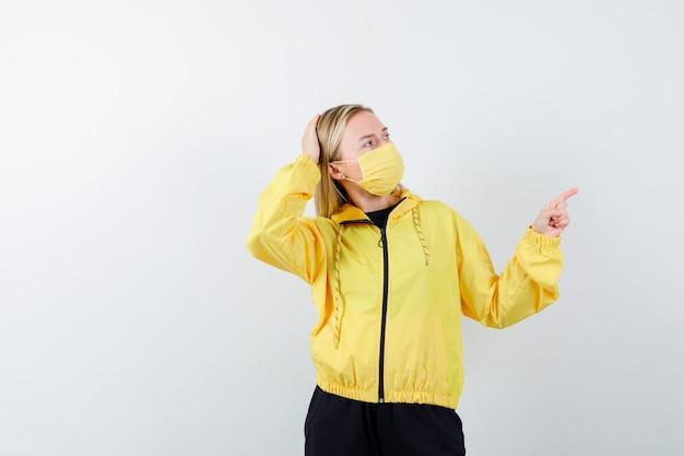 Portrait de jeune femme pointant vers le coin supérieur droit, gardant la main sur la tête en survêtement, masque et à la vue de face pensive