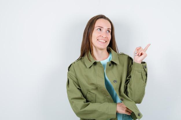 Portrait de jeune femme pointant vers le coin supérieur droit en veste verte et à la vue de face joyeuse