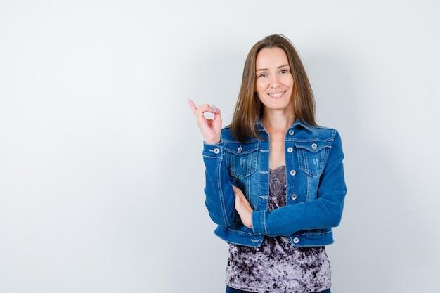 Portrait de jeune femme pointant vers le coin supérieur gauche en blouse, veste en jean et à la vue de face joyeuse