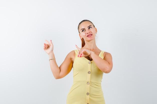 Portrait de jeune femme pointant vers le coin supérieur gauche, regardant en robe jaune et à la vue de face pensive