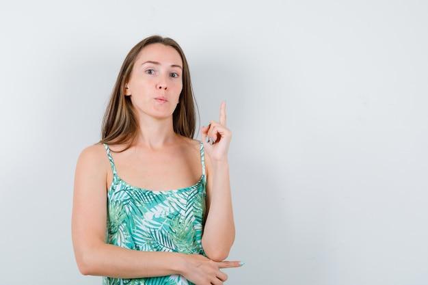 Portrait de jeune femme pointant vers le haut en blouse et à la vue de face confiant