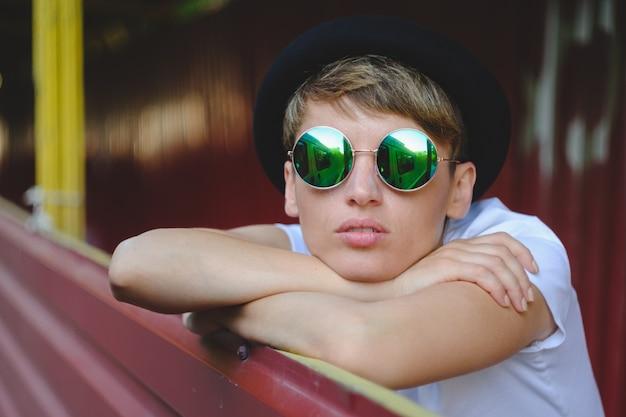 Portrait de jeune femme portant un chapeau élégant et des lunettes rondes