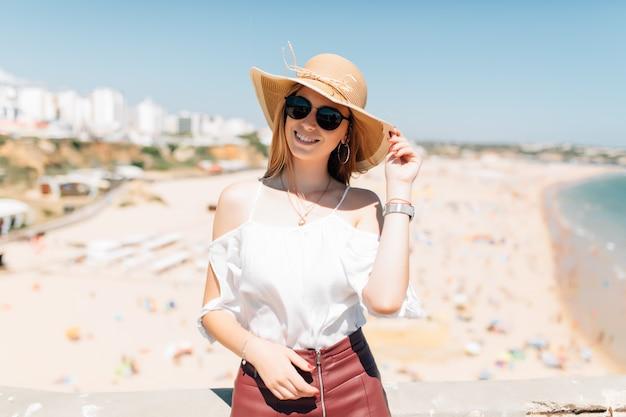 Portrait de jeune femme portant chapeau et lunettes de soleil rondes, beau temps venteux journée d'été sur l'océan