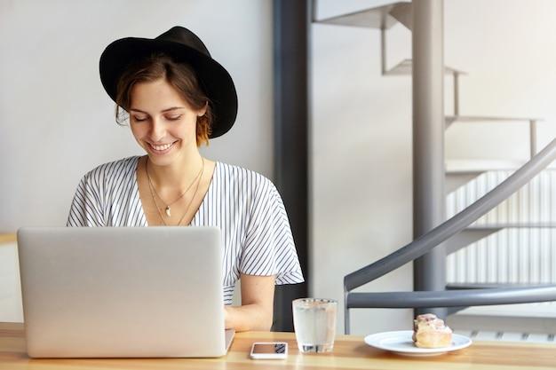 Portrait de jeune femme portant un grand chapeau et utilisant un ordinateur portable