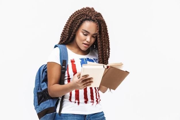 Portrait de jeune femme portant un livre de lecture de sac à dos tout en étudiant au collège debout isolé contre un mur blanc
