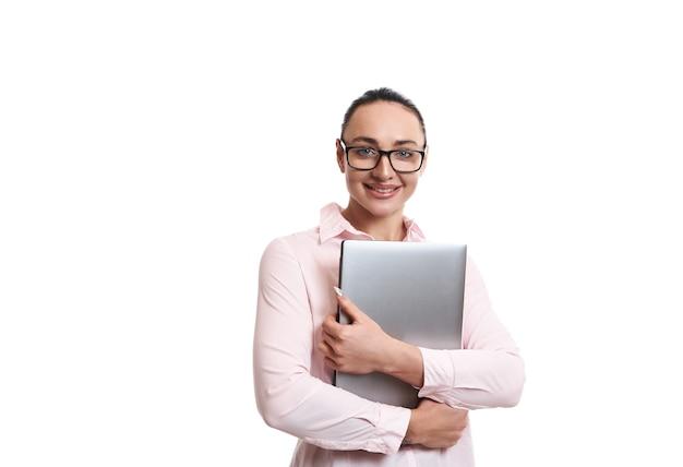 Portrait d'une jeune femme portant des lunettes, tenant un ordinateur portable dans les mains, souriant tout en posant sur fond blanc avec espace copie