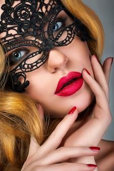 Portrait de jeune femme portant un masque de soirée en dentelle noire
