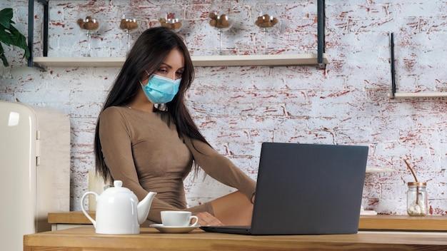 Portrait de jeune femme portant un masque et travaillant sur ordinateur dans la cuisine