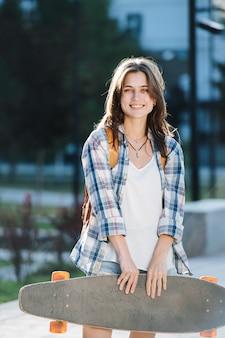 Portrait d'une jeune femme posant avec une planche à roulettes dans un parc le matin