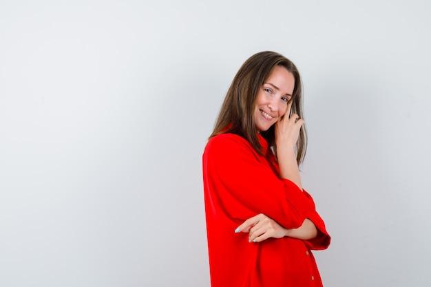 Portrait de jeune femme posant tout en touchant la joue en blouse rouge et à la vue de face délicate
