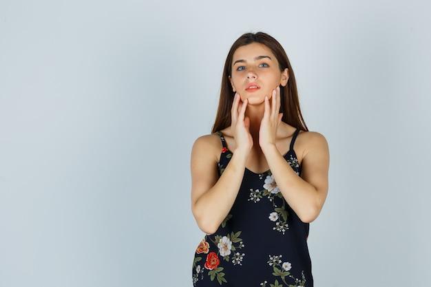 Portrait de jeune femme posant tout en touchant son menton en chemisier et l'air gracieux. vue de face.