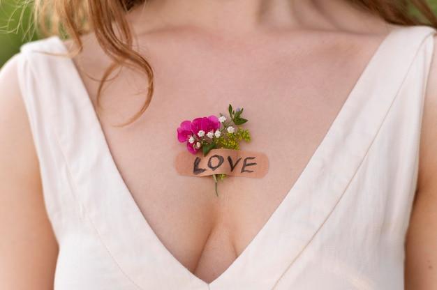 Portrait de jeune femme posant en toute confiance à l'extérieur avec des fleurs