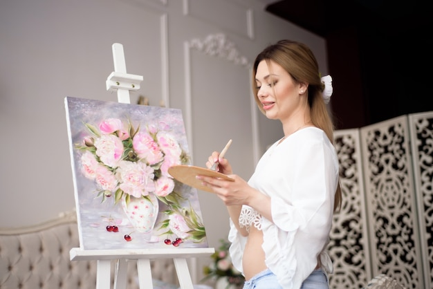 Portrait d'une jeune femme pragnant peinture avec des peintures à l'huile sur toile blanche, portrait vue de côté