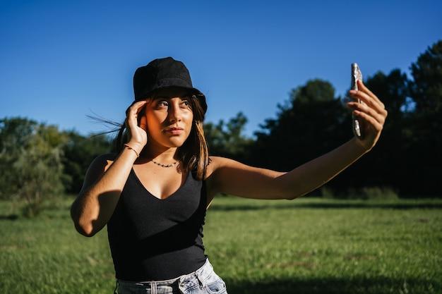 Portrait de jeune femme prenant un selfie avec un smartphone dans un champ