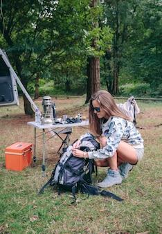 Portrait de jeune femme préparant un sac à dos pour une randonnée dans la forêt