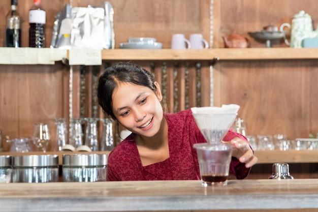 Portrait de jeune femme prépare un verre avec une passoire à thé