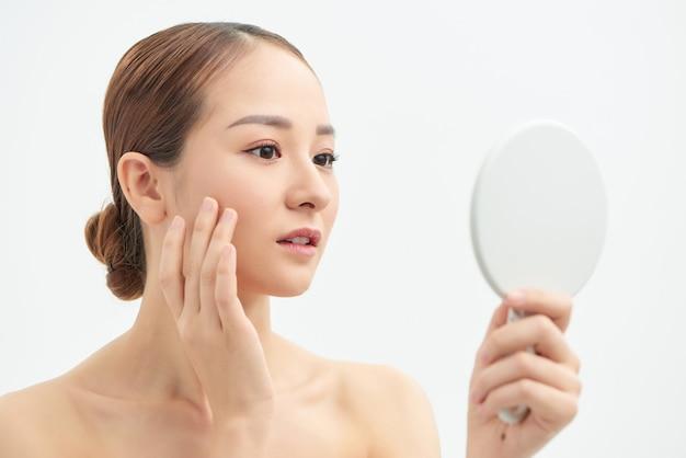 Portrait de jeune femme avec problème d'acné regardant dans un miroir sur fond blanc
