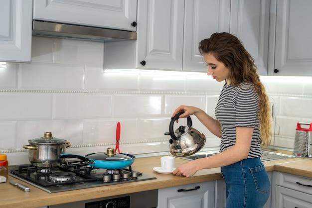 Portrait de jeune femme profiter du café ou du thé dans la cuisine. matin de rêve