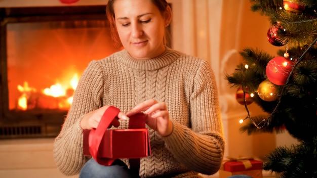Portrait de jeune femme en pull assis à côté d'un foyer en feu et emballer des cadeaux et des cadeaux de noël