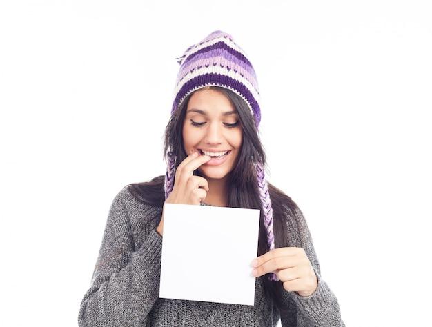 Portrait de jeune femme avec un pull et un chapeau péruvien en laine tenant la carte de signe. fond blanc . isolé