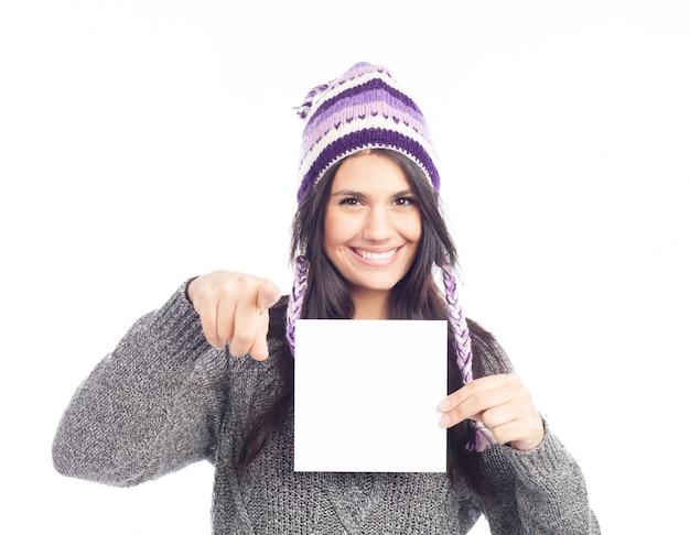 Portrait de jeune femme avec un pull et un chapeau péruvien en laine tenant une carte de signe