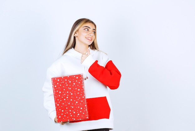 Portrait de jeune femme en pull chaud avec cadeau de noël montrant le pouce vers le haut