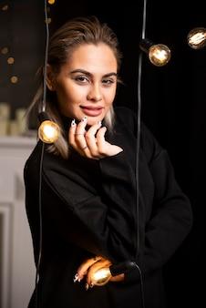 Portrait de jeune femme en pull noir debout et posant