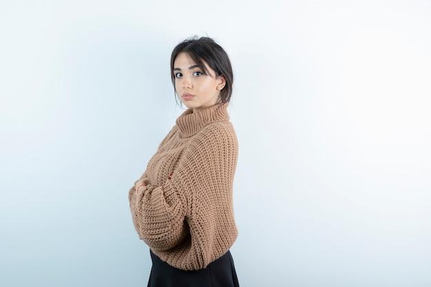 Portrait de jeune femme en pull tricoté posant sur un mur blanc