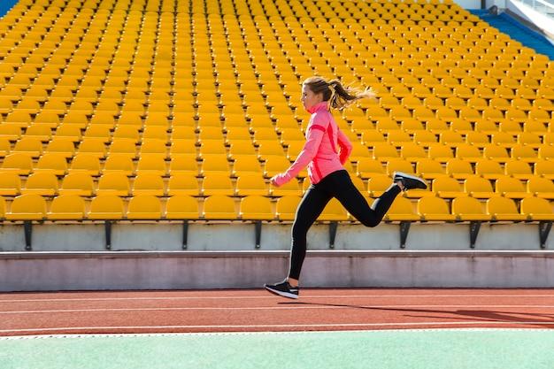 Portrait d'une jeune femme qui court au stade