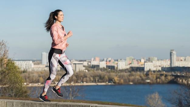 Portrait de jeune femme qui court en plein air