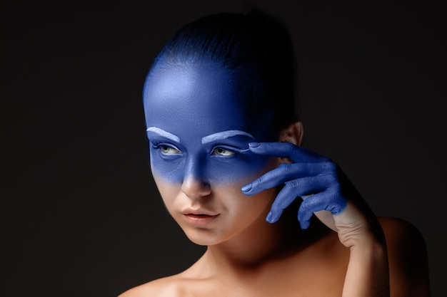 Portrait d'une jeune femme qui pose recouverte de peinture bleue en studio sur fond noir. la main de la fille autour du visage et peinte en bleu