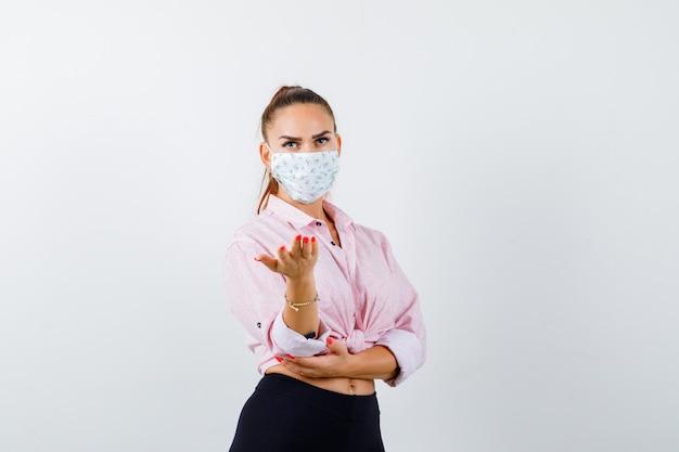 Portrait de jeune femme qui s'étend de la main en geste perplexe en chemise, pantalon, masque et à la vue de face sérieuse