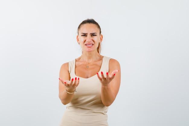 Portrait de jeune femme qui s'étend les mains vers la caméra en débardeur beige et à la vue de face triste