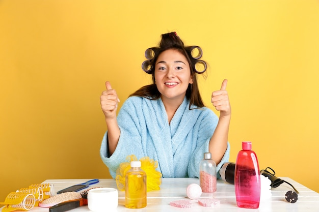Portrait de jeune femme de race blanche dans sa routine de soins de jour, de peau et de cheveux de beauté. modèle féminin avec des cosmétiques naturels appliquant de la crème et des huiles pour le maquillage. soins du corps et du visage, concept de beauté naturelle.