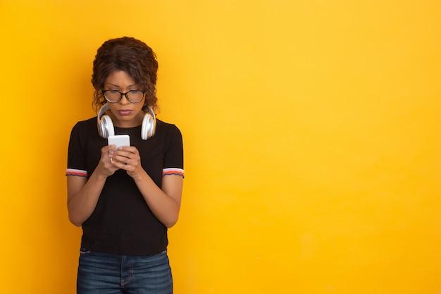 Portrait de jeune femme de race blanche avec des émotions vives sur jaune