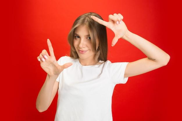 Portrait de jeune femme de race blanche avec des émotions vives sur rouge vif