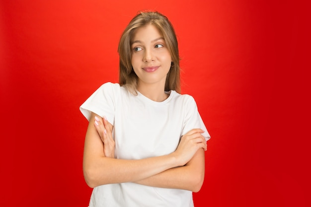 Portrait de jeune femme de race blanche avec des émotions vives sur studio rouge